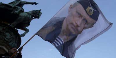 A man waves a flag showing Russian President Vladimir Putin in front of the monument of late Serbian Duke Mihailo Obrenovic, during a meeting to show their support for a referendum in Republika Srpska, in Belgrade, Serbia, Saturday, Sept. 24, 2016. Bosnia's Serb mini-state is holding a referendum this weekend that has turned into a proxy political battle between the West and Russia, stoking ethnic tensions and triggering fears of new clashes more than 20 years after the end of the Balkans War. (AP Photo/Darko Vojinovic)