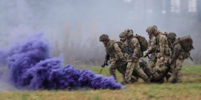 """ELVAL, NORWAY - NOVEMBER 03: British soldiers from Anzio Company of the Duke of Lancaster Regiment carry a """"wounded"""" colleague through a smoke screen, during the live exercise on November 3, 2018 in Elval, Norway. Over 40,000 participants from 31 nations are taking part in the NATO """"Trident Juncture"""" exercise to test inter-operability between forces, and is the largest exercise of its kind to be held in Norway since the 1980s. (Photo by Leon Neal/Getty Images)"""